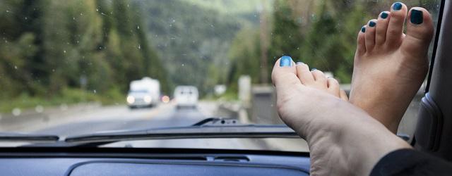 piedi sul cruscotto auto